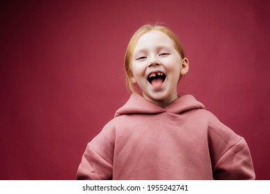 a 7-year-old girl without one upper tooth smiles in a hoodie on a pink background. Studio photography