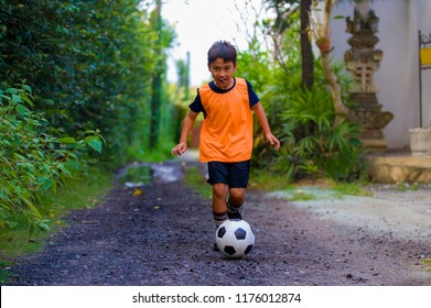 8 or 9 years old happy and excited kid playing football outdoors in garden wearing training vest running and kicking soccer ball , the kid having fun practicing sport