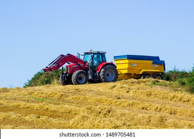 8 August 2019 A large Massey Ferguson tractor and trailer in a County Down field in Northern Ireland during the barley harvest.