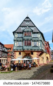 8 August 2019: Oldest Hotel from1158  (alteste Gasthaus Deutschlands), half-timbered houses, restaurant, shops, peaple in old german town Miltenberg am Main river. Odenwald, Bavaria, Germany