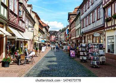 8 August 2019: Street with colorful half-timbered houses, peaple, restaurants, shops in  old german town Miltenberg am Main river,. Odenwald, Bavaria, Germany