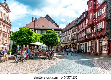 8 August 2019: View on Marketplace (Alter Marktplatz) with half-timbered houses, peaple, restaurants in old german town Miltenberg am Main river, Odenwald, Bavaria, Germany