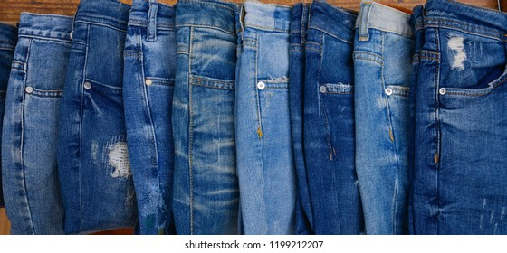 8 blue jeans on wooden background. Assortment. Fashionable concept