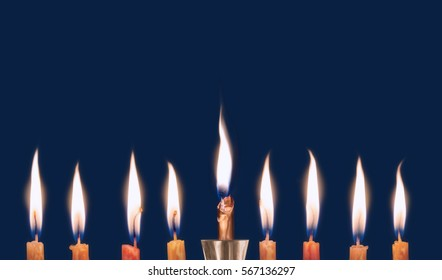 8 chanukah candles burning low isolated on dark blue background. Large bright glowing flames. Close up view. Room for text.