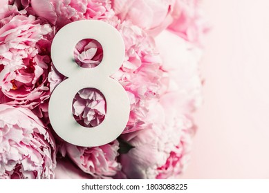8 March. Happy Women's Day. Creative layout. Pink peony flowers and digit eight 8. Birthday greeting card. Anniversary concept. Top view. White numeral over flowers background. Numerical digit