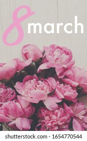 8 March text. 8 march lettering on stylish pink peonies rustic flat lay. Floral greeting card. Happy Women's day. Beautiful peony flowers, tender image