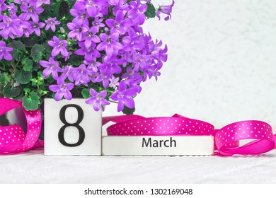 8 March wooden block calendar.Women's day conceptual background with Campanula flower and pink ribbon on white wooden background.Holiday calendar greeting card
