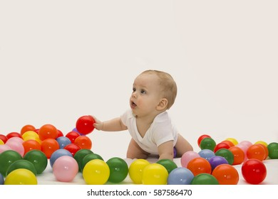 8 month baby boy playing with color balls. White background