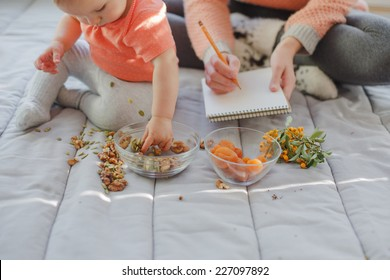 8 month old baby sitting next to the mother who is painting. The baby is taking different seeds, nuts and dried apricots to discover their taste and form