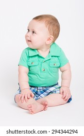 8 month year old baby sits on a white background looking off camera. dressed in a cute green polo shirt and blue plaid shorts.