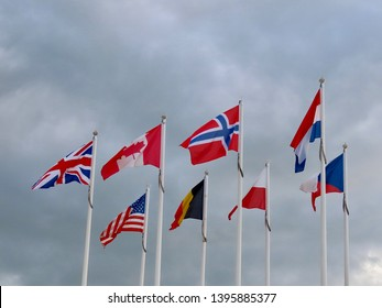 8 national flags by the museum of D-Day (6th June 1944) in Arromanches, France on a cloudy and windy day