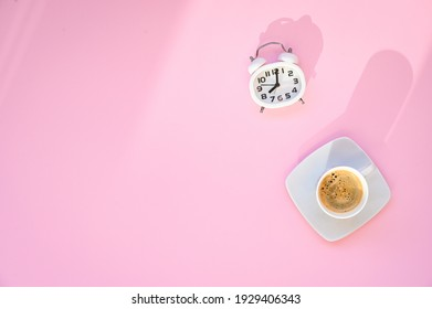 8 oclock on a alarm clock. Good morning with a cup of coffee espresso and white clock on a pink background. breakfast blogging content. Top view with copy space