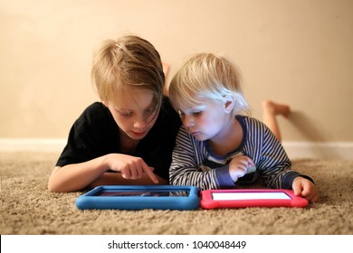 An 8 year old big brother is showing is little sister how to play a game on their electronic tablets, as they lay on the carpet in their home.