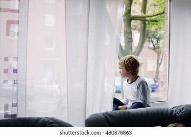 8 year old boy sitting near the window and looking to the street