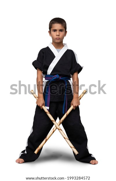 8 year old boy wearing a black martial arts kimono doing martial arts poses on a white background.