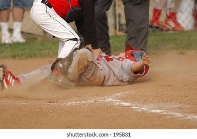 8 year old pony league player sliding into home plate