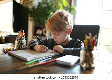 An 8 year old school aged child is working on a coloring art project, using colored pencils to draw on white paper.