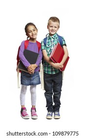 8 year old school boy and girl with backpacks holding books smiling on white background