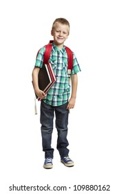 8 year old school boy with backpack holding books on white background