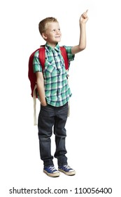 8 year old school boy with backpack pointing on white background