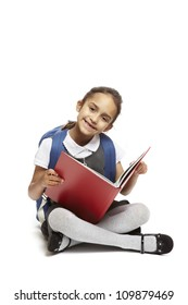 8 year old school girl with backpack sitting reading red book smiling on white background