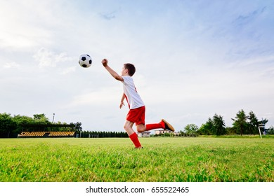 8 years old boy child playing football on playing field. Child playing football
