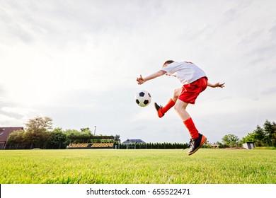 8 years old boy child kicking ball on playing field. Child playing football