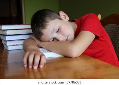 8 years old boy doing his boring homework and sleeping