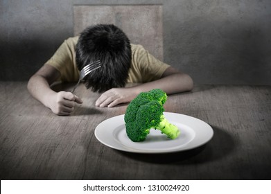 8 years old disgusted and displeased child refusing to eat healthy green broccoli feeling upset in kid nutrition education on healthy fresh food and young boy hating eating vegetarian meal