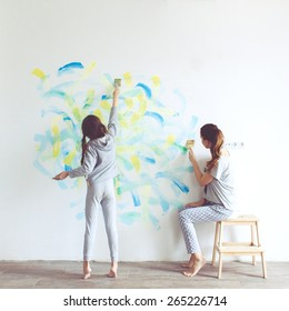 8 years old girl painting the wall at home, Instagram style toning