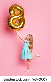 I am 8 years old! Vertical full-length side profile view portrait of cute lovely beautiful girl celebrating birthday, she is holding golden balloon in shape of figure-eight isolated on pink background