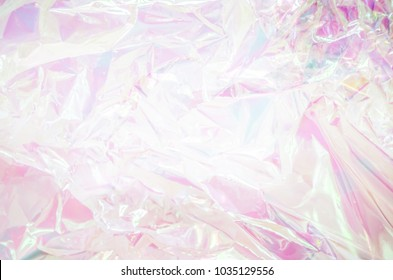 80s, 90s background. Holographic abstraction - TRENDY colorful texture in pastel colors. Very beautiful iridescent texture. Holography foil. Hologram background of wrinkled abstract foil texture