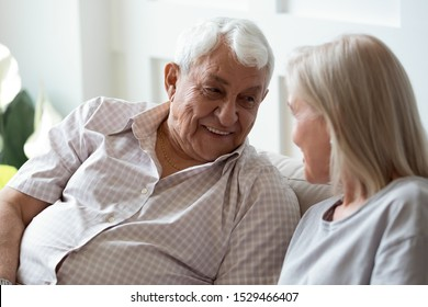 80s man seated on sofa talking with middle-aged woman, old father and adult daughter chatting having pleasant positive conversation at home, elderly spouses spend time speak share memories feels happy