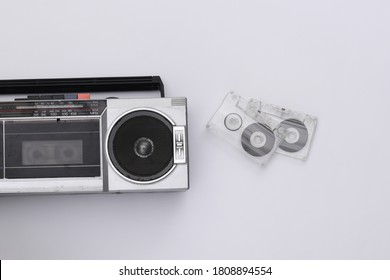 80s Retro outdated portable stereo radio cassette recorder and audio cassette on white background. Top view. Flat lay
