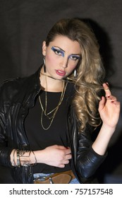 80s style girl posing on black background. Make up and hair look is retro