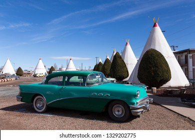 811 West Hopi Drive, Holbrook, Arizona, USA, February 20, 2019 - Classic turquoise vintage car parked in front of iconic concrete tipis of the 1937 Wigwam Motel, on route 66