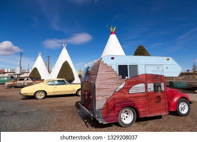 811 West Hopi Drive, Holbrook, Arizona, USA, February 20, 2019 - Vintage camping car parked in front of iconic concrete tipis of the 1937 Wigwam Motel, on route 66