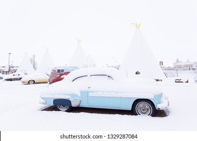 811 West Hopi Drive, Holbrook, Arizona, USA, February 20, 2019 - Classic pale blue vintage car parked in front of iconic concrete tipis of the 1937 Wigwam Motel under a layer of fresh snow