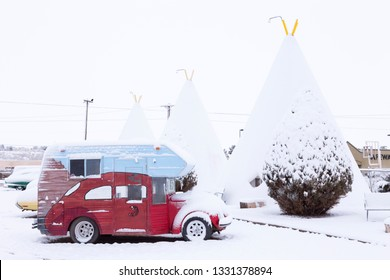 811 West Hopi Drive, Holbrook, Arizona, USA, February 21, 2019 - Vintage camping car parked in front of iconic concrete tipis of the 1937 Wigwam Motel under a layer of fresh snow