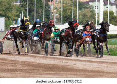 "8.26.2018 Russia, Moscow, Central Moscow hippodrome. Tests of horses of trotters on the prize ""Cup of Miners"". Many horses harnessed in two-wheeled crew compete in speed trot"