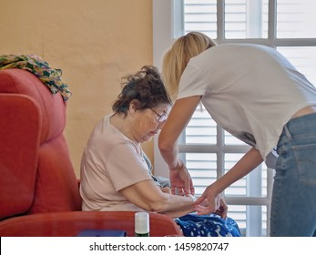 An 83-year-old senior in her wing chair and the geriatric nurse helps her  to cover a wound with plaster.