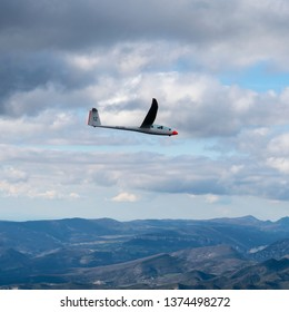 8-4-2019, Saillans, France. Aerial view of glider Duo Discus PH-1198 in the French Alps. This sailplane is owned by gliding club EZZC. Many white clouds and a mountain area.
