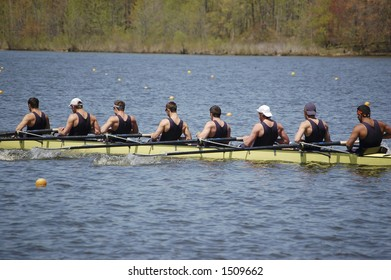 An 8-man crew team pulls together toward the end of their race