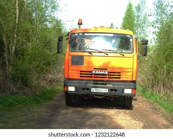 8th of May 2018 - Scene from Russian forest road with orange Kamaz truck, Leningrad Oblast, Russia