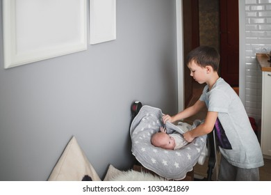 The 8-year-old boy carefully covers his newborn sister with a blanket. Cozy bright kitchen. On the walls hang white picture frames.