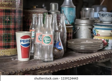 9 August 2018,Nakornrachasima,Thailand. old and dirty collection bottle and glass with old logo brand on shelf in vintage object concept