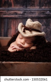 9 day old newborn baby boy wearing a crocheted cowbow hat and sleeping on  his stomach cac2b665b156