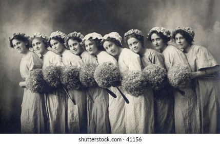 9 Maids a Cleaning - nine young, cleaning women with their dust mops. A circa 1900, vintage photograph.
