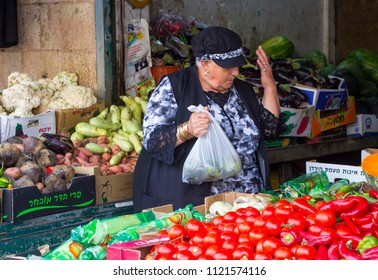 9 May 2018 A plump female stall holder with her hand raised as she fills a plastic bag with fresh vegetables at the Mahane Yehuda market in Jerusalem Israel