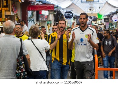 9 May 2018 Singing and chanting football supporters in Beitar Jerusalem strip march down the mall of the Mahane Yehuda covered market in Jerusalem Israel before their match with  Hapoel Haifa